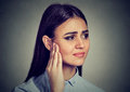 Tinnitus. Sick female having ear pain touching her painful head Royalty Free Stock Photo