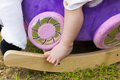 Tiny baby's foot on toy rocking horse Royalty Free Stock Photo