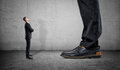Tiny businessman looking up on huge legs of another man Royalty Free Stock Photo
