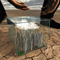 Tiny city in plastic box in desert landscape about to be picked up by giant Royalty Free Stock Photography