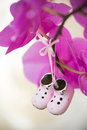 Tiny decorative collectible shoes hanging on orchid flower shallow depth of field Royalty Free Stock Photography