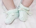 Tiny feet of baby in a bootees light green Stock Photo