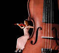Tiny female violinist playing a violin sitting on the edge of the big one over black background Stock Photos