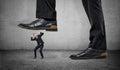 Tiny frightened businessman under feet of huge man