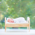 Tiny newborn baby in toy bed next to big window Royalty Free Stock Photo