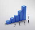Tiny people standing around a bar graph teamwork and company profits concept Royalty Free Stock Photography