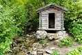 Tiny wooden mountain cabin in dense lush green summer forest with a small creek beside it