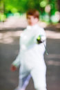 Tip of rapier held by fencer woman staying in park alley shallow depth field Royalty Free Stock Images