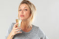 Tipsy young blond woman drinking bubbly wine female drinker a flute of suffering from booze addiction gray background Stock Photography