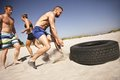 Tire flip crossfit exercise on beach strong male athlete about to a truck young people doing a sunny day Royalty Free Stock Photo