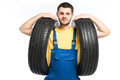 Tire service worker in blue uniform holds car tyre Royalty Free Stock Photo