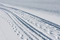 Tire tracks and footsteps in white snow Royalty Free Stock Images