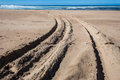 Tire tracks x beach sand close up vehicle in the ocean sands photo detail against the horizon blue sea sky Stock Images
