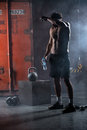 Tired athlete topless wipes the sweat from his forehead in hand a bottle of water studio shot in dark tone Royalty Free Stock Photo