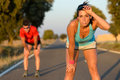 Tired athletes after running hard fitness couple of runners sweating and taking a rest during marathon training in country road Stock Image