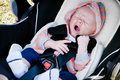 Tired baby in car seat a yawning boy sitting a rear facing infant Royalty Free Stock Photography