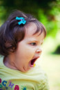 Tired baby girl yawning outdoors in park Royalty Free Stock Images