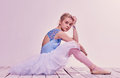 Tired ballet dancer sitting on the wooden floor Royalty Free Stock Photo