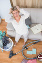 Tired blonde cleaning her chaotic living room at home Royalty Free Stock Image