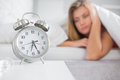 Tired blonde staring at her alarm clock home in bedroom Stock Images