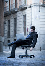 Tired Business Man sitting on Office Chair on Street sleeping Royalty Free Stock Images