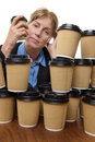 Tired business woman and disposable cups mature is sitting at her desk surrounded by takeaway looking very Stock Image