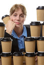 Tired business woman and disposable cups mature is sitting at her desk surrounded by takeaway looking very isolated on white Stock Image