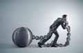 Tired businessman dragging heavy chains