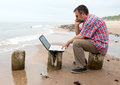 Tired businessman sitting with notebook on beach senior Royalty Free Stock Photography
