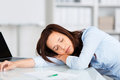 Tired businesswoman having a nap at her desk with her head lying on her arm facing the camera Royalty Free Stock Photography
