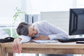 Tired businesswoman sleeping at her desk in office Royalty Free Stock Photo