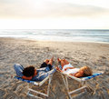 A tired couple resting on the deck chairs Royalty Free Stock Photo