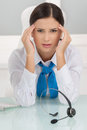 Tired customer service representative depressed young female sitting at her working place and holding her head in hands Royalty Free Stock Images