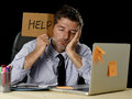 Tired desperate businessman in stress working at office computer desk holding sign asking for help Royalty Free Stock Photo
