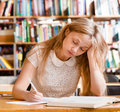 Tired female student n library Royalty Free Stock Photo