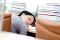 Tired female student sleeps at the desk Stock Photos