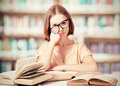 Tired funny girl student with glasses reading books crazy in the library Stock Photo