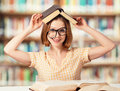 Tired funny girl student with glasses reading books crazy in the library Royalty Free Stock Photo