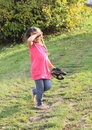 Tired girl walking barefoot little with plaits in pink t shirt and grey jeans on green grass with black shoes holded in hand Royalty Free Stock Image