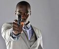 A tired handsome young black business man aims his handgun directly into the camera Stock Photography