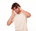 Tired handsome young man having a headache portrait of with hand on head while standing on white background Stock Photography