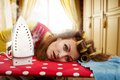 Tired housewife with ironing board lying on Royalty Free Stock Photography
