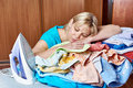 Tired housewife sleeping on an ironing board Royalty Free Stock Photo