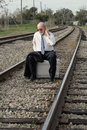Tired jobless senior businessman sits on suitcase on train track Royalty Free Stock Photography