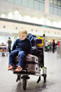 Tired little boy sitting on suitcases on international airport