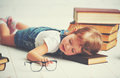 Tired little girl fell asleep for books Royalty Free Stock Photo
