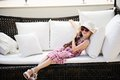 Tired little girl relaxing on terrace divan in pink dress and white hat sofa Royalty Free Stock Photography