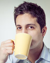 Tired man drinking coffee in the morning retro style image of a from a yellow cup Royalty Free Stock Photos