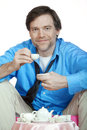 Tired man in forties having a tea party but happy caucasian drinking from child s teacup at while sitting on pink beanbag Royalty Free Stock Photography