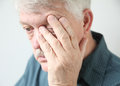 Tired man rubbing his eye overworked senior rubs an in fatigue Stock Photo